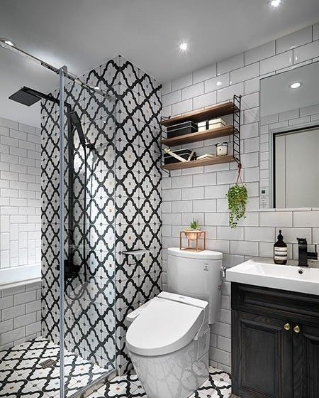卫生间淋浴区的墙面和整体地面采用黑白的花砖,再用玻璃推拉隔断